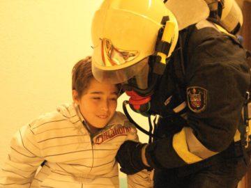 Feuerwehrmann hilft Junge